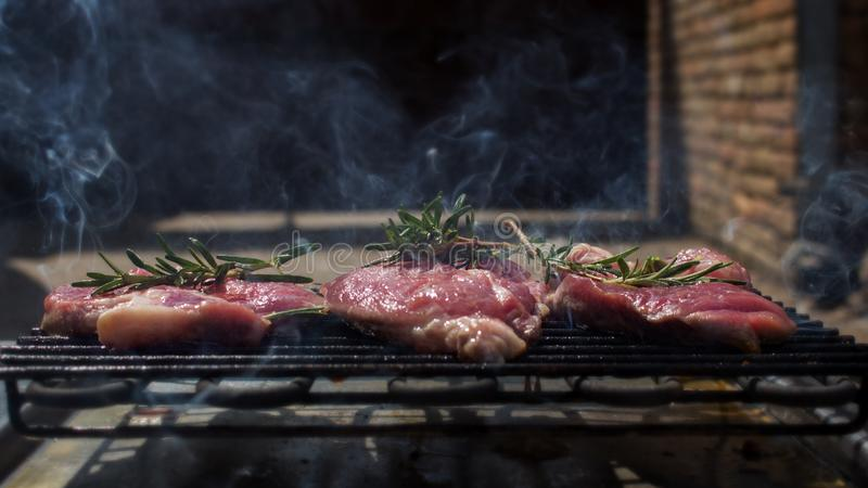 Pork Steaks With Rosemary Grilling on Hot Barbecue. Pork Steaks With Rosemary Grilling on a Hot Barbecue stock image