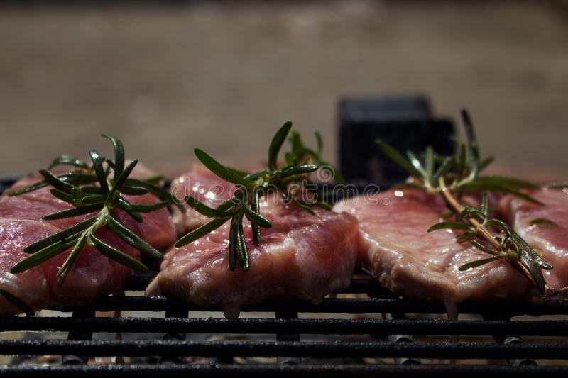 Pork Steaks With Rosemary Grilling on Hot Barbecue. Pork Steaks With Rosemary Grilling on a Hot Barbecue royalty free stock photo