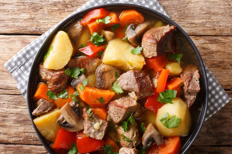 Pork stew with mushrooms, potatoes, carrots and peppers close-up on a plate. horizontal top view stock images