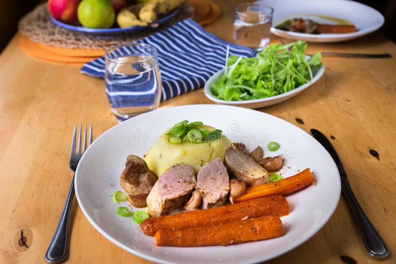 Pork tenderloin,mashed potato and carrot on plate, salad on wooden table stock photo