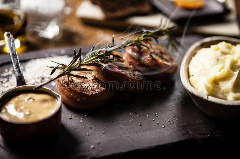Pork tenderloin served on a board in restaurant royalty free stock photography