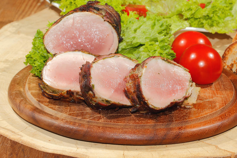 Pork tenderloin, pork medallions, grilled, pork, meat, bacon. Pork tenderloin, pork medallions, pork, meat wrapped in bacon, grilled and garnished with lettuce stock photography