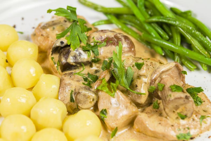 Pork tenderloin with potatoes and wild mushroom sauce and green beans on white plate stock photo
