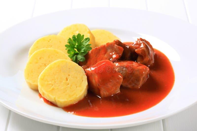 Pork in tomato sauce with potato dumplings. Pork meat in tomato sauce served with potato dumplings stock photography
