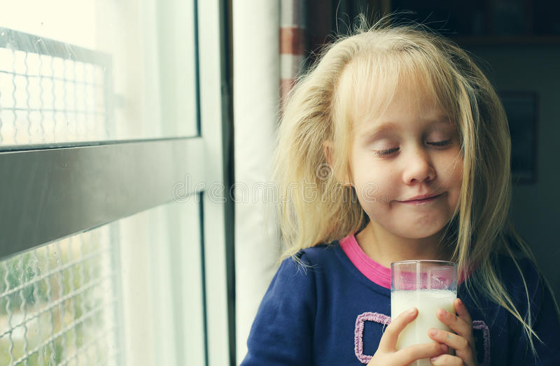 Porrait of 5 years old girl. 5 years old girl holding glass of milk royalty free stock images