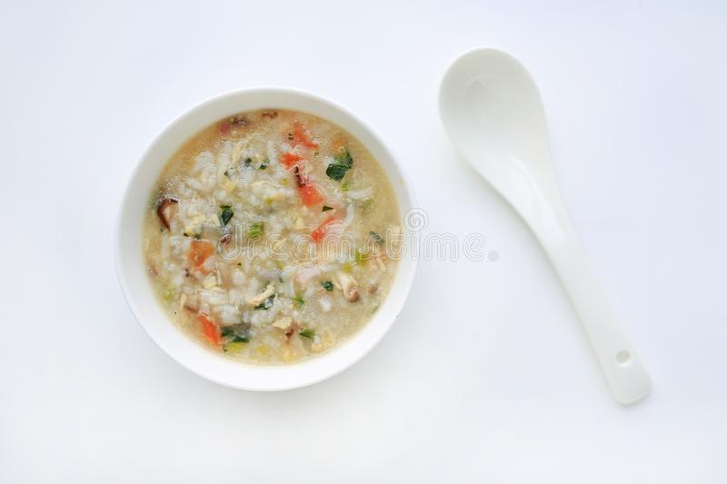 Porridge for baby food in white ceramic bowl and spoon on white background royalty free stock photography