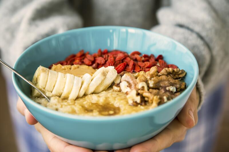 Porridge bowl in woman hands. Front view of cozy warm winter healthy oatmeal with goji fruits and nuts stock image