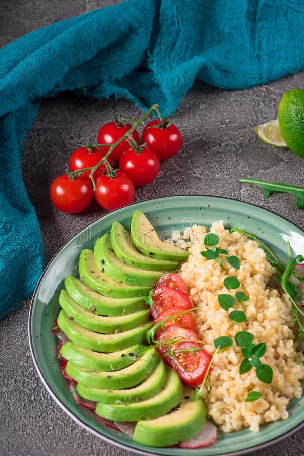 Porridge bulgur with salad avocado, tomatoes and arugula. Rustic concrete background. Top view.  stock photography