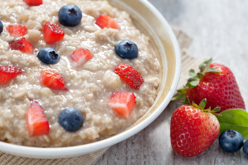 Porridge. Close up view of oatmeal porridge with strawberry on color back stock photography