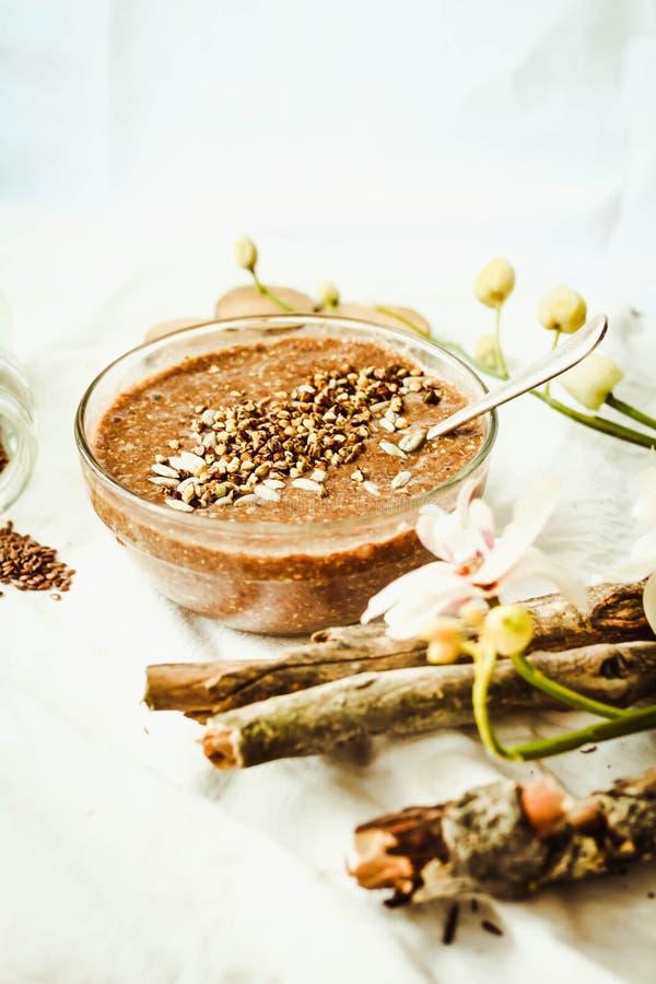 Porridge crudo dai semi di lino con cacao, la banana e il buckwh verde immagini stock libere da diritti