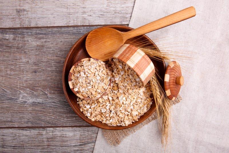 Porridge crudo in una ciotola con un cucchiaio di legno su un tovagliolo della tela di sacco, su una tavola di legno marrone fotografia stock libera da diritti