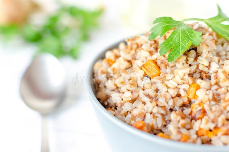 Porridge de sarrasin avec carottes et persil dans une plaque bleue Sur fond d'oignons d'or et de persil vert photo libre de droits
