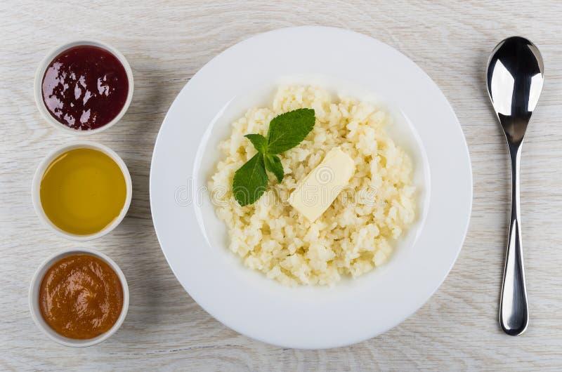 Porridge del riso con burro, menta in piatto, inceppamento, miele, cucchiaio fotografia stock