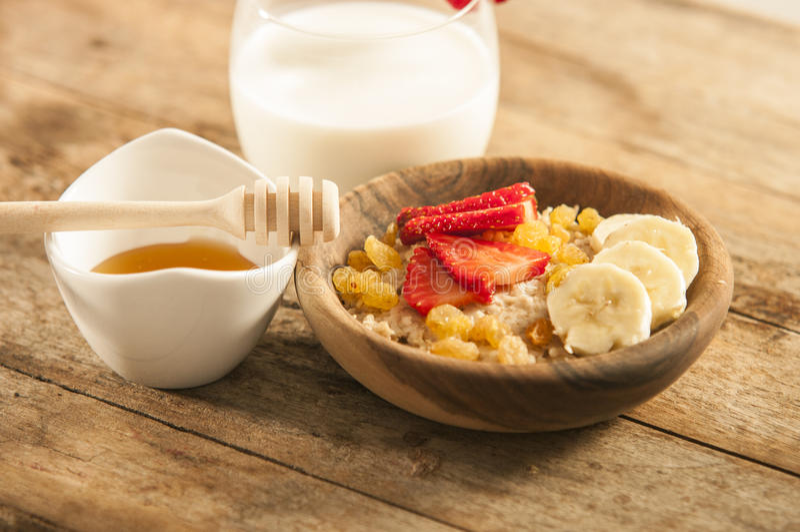 Porridge della farina d'avena con la fragola e la banana in ciotola di legno immagini stock libere da diritti