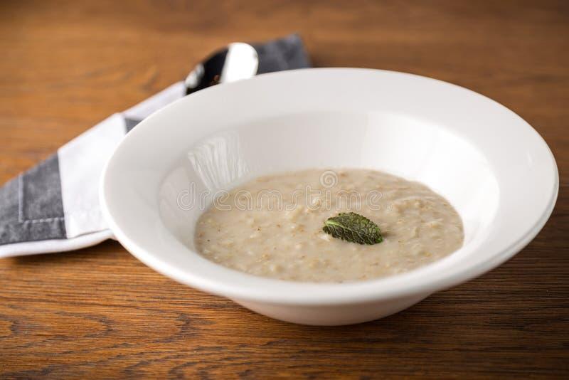 Porridge della farina d'avena sul piatto bianco con il cucchiaio su fondo di legno fotografia stock