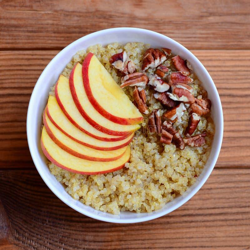 Porridge della quinoa della prima colazione del dado e della frutta Porridge della quinoa con le mele ed i pecan freschi in una c immagine stock libera da diritti
