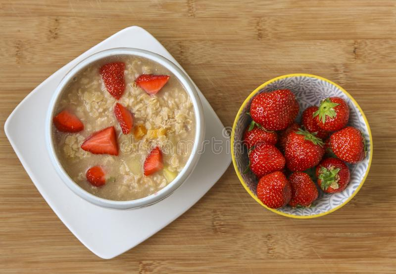 Porridge and fresh strawberries in a bowl. royalty free stock photo