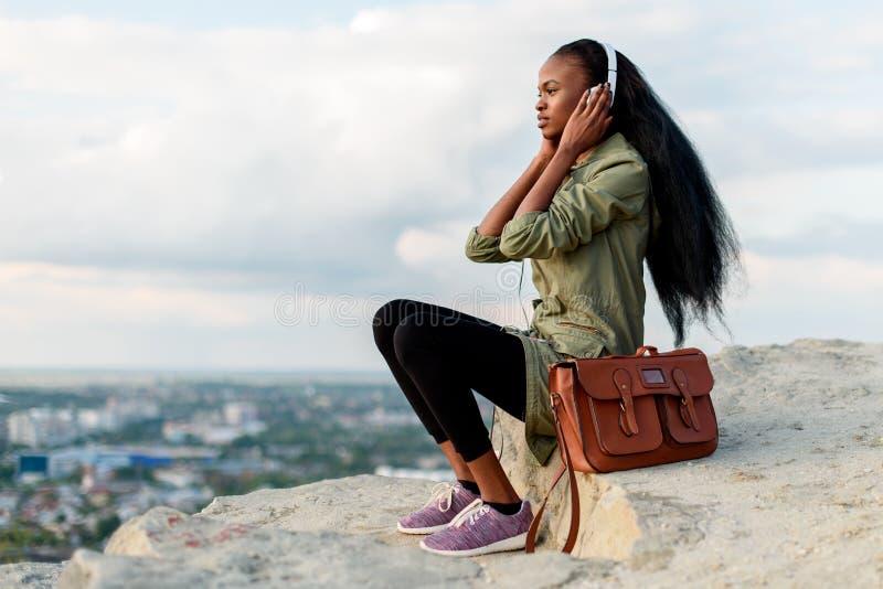 Porrtrait de la mujer afroamericana magnífica del inconformista con smartphone y de auriculares que escuchan la música sobre nubl fotos de archivo libres de regalías