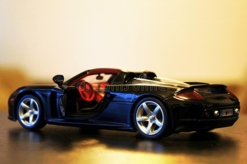 Porsche Carrera GT model racing car - open door. Porsche Carrera GT sport car - die-cast metal model toy 1:24 scale, Black. Lateral view. Open door, visible stock images