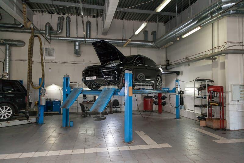Porsche Cayenne, carro preto usado com capuz aberta levantada em um elevador de quatro postes para reparar o chassi e o motor de  foto de stock