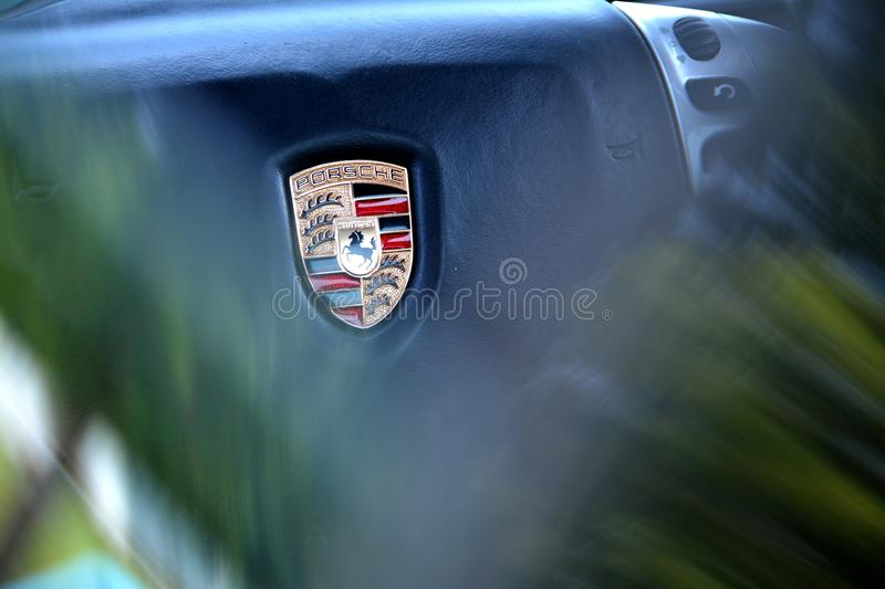 Porsche logo. Porsche car logo blured steering wheel royalty free stock photography