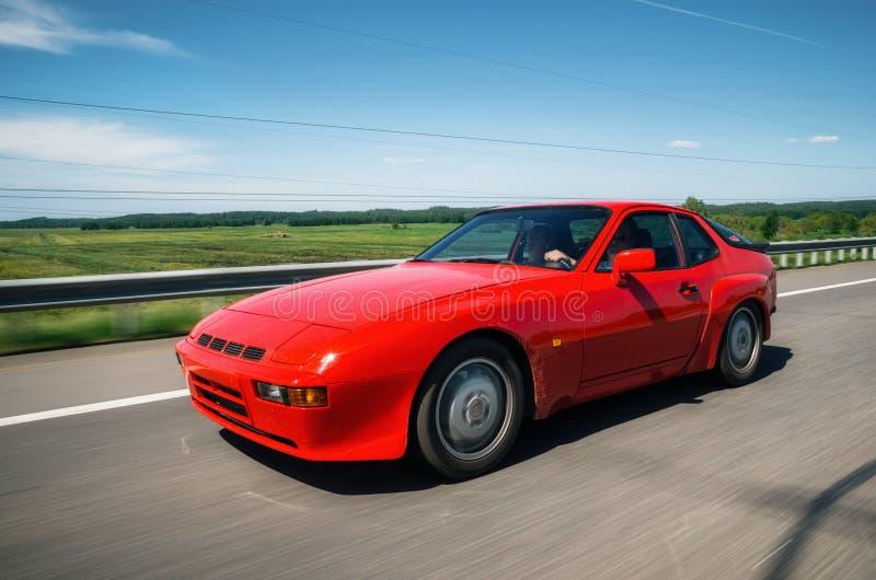 Porsche rosso 944 si muove lungo la strada immagini stock