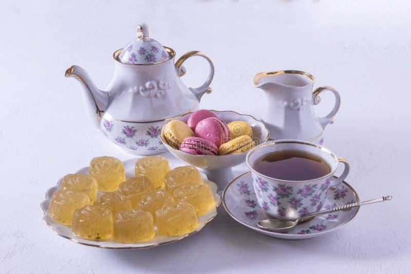 Porseleintheestel met melk, macaroni en marmelade, melkkruik, theekop, kop en schotel, kleverig suikergoed stock fotografie