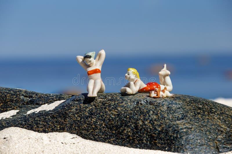 Porslindiagram av att solbada flickor på en granitsten royaltyfria foton