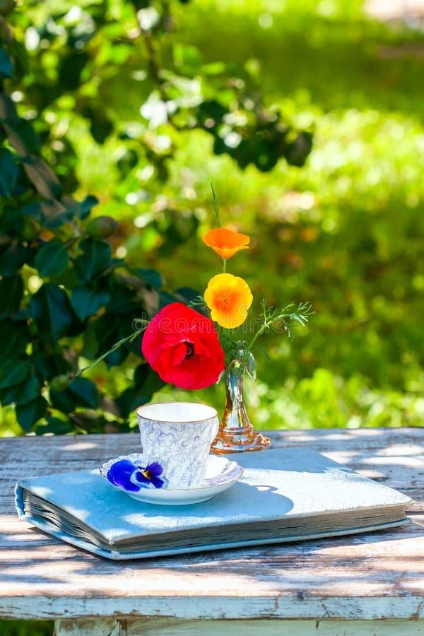 Porslinkopp te och den härliga våren blommar i vas på en trätabell i trädgården Sommarparti arkivbild