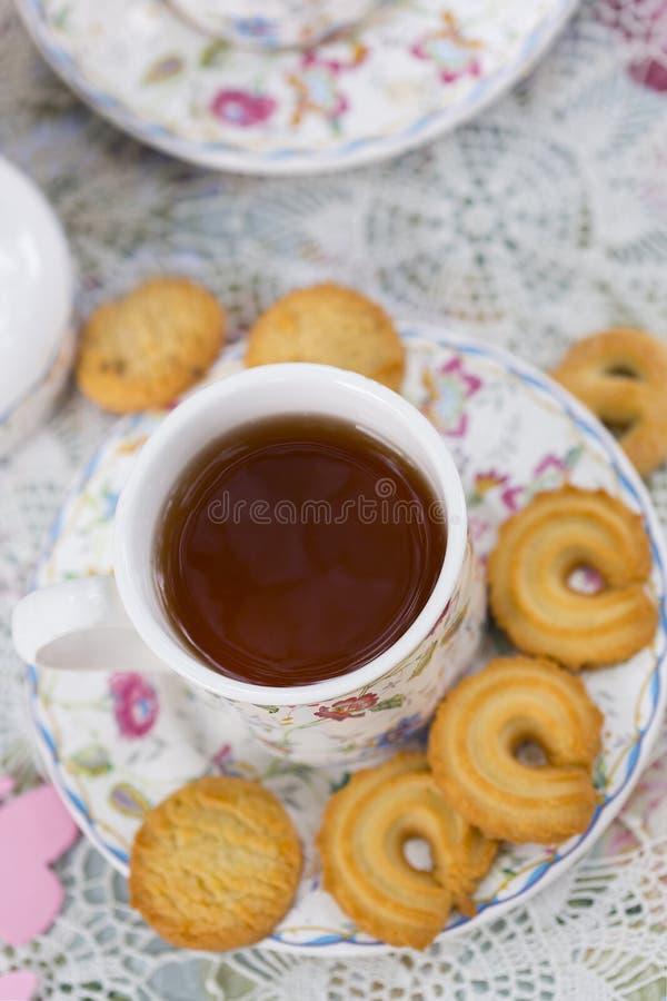 Porslinkopp te- och sockerkakan är på tabellen fotografering för bildbyråer