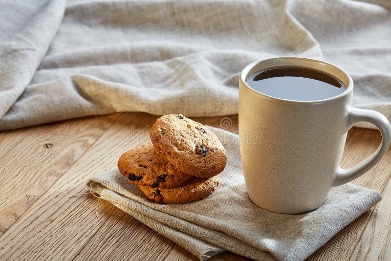 Porslintekopp med kakor för chokladchiper på bomullsservetten på en lantlig träbakgrund, bästa sikt, närbild arkivfoton
