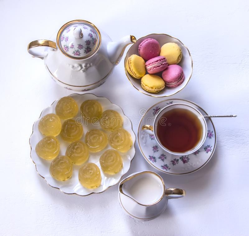 Porslinteservisen med mjölkar, makaroni, och marmelad, mjölkar tillbringaren, tekoppen, koppen och tefatet, klibbig godis royaltyfria bilder