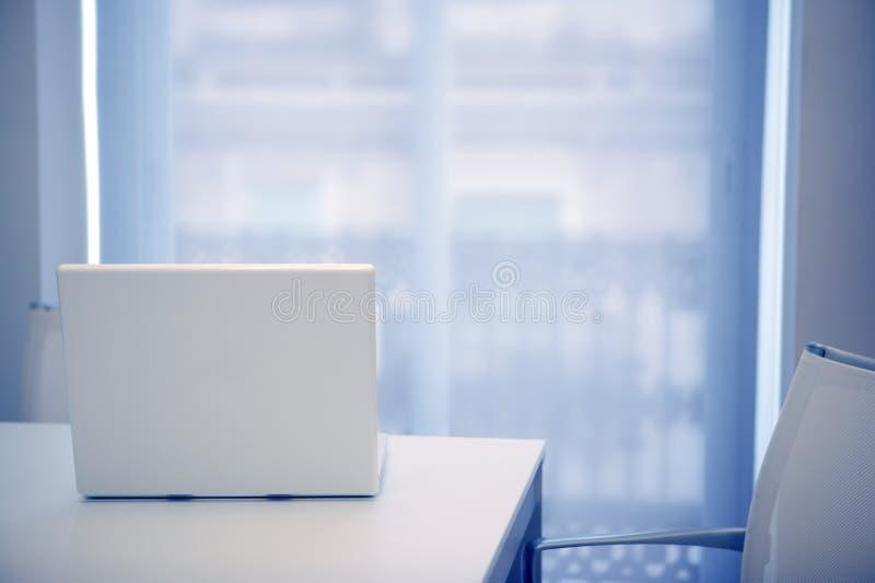 Portátil branco aberto em um quarto branco, luz azul fotografia de stock