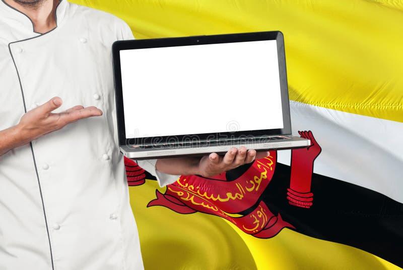 Portátil Bruneian da terra arrendada do cozinheiro chefe com a tela vazia no fundo da bandeira de Brunei Darussalam Cozinhe o uni foto de stock