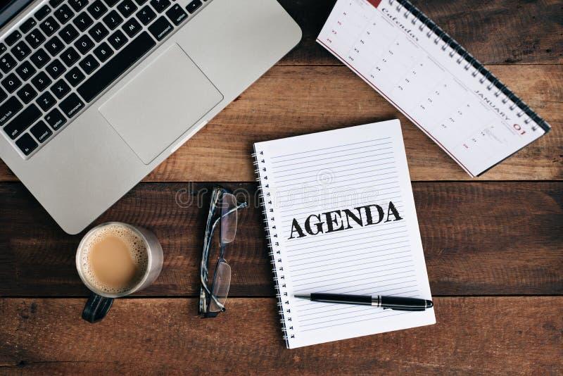 Portátil, caderno, vidros, caneca de café e calendário com palavra da AGENDA na tabela de madeira imagens de stock