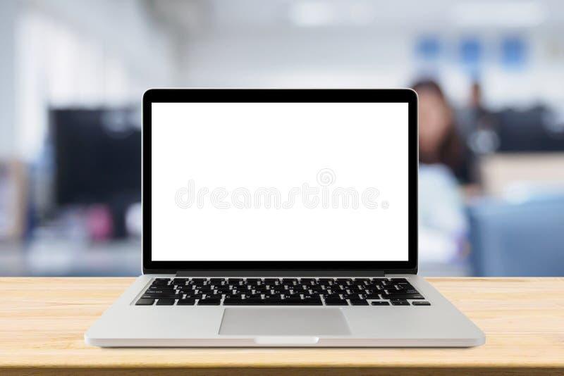 Portátil com a tela vazia na tabela da mesa com interior do escritório do borrão fotografia de stock