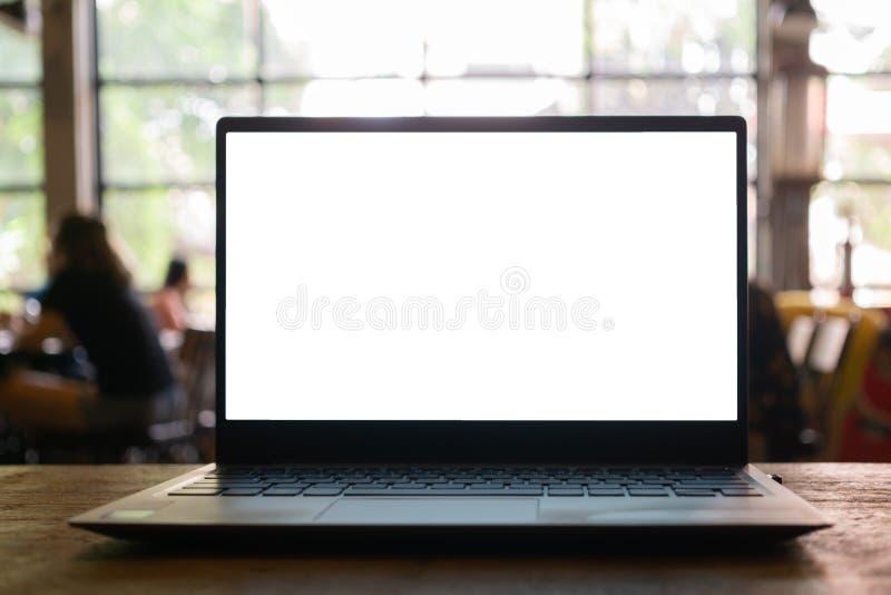 Portátil com a tela vazia na tabela com fundo borrado da cafetaria foto de stock royalty free