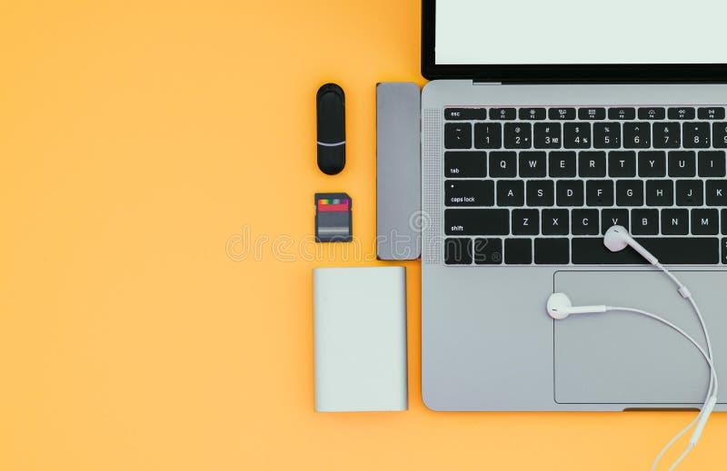 Portátil com tipo-c adaptador, movimentações instantâneas, fones de ouvido e banco em um fundo amarelo, vista superior de USB do  imagens de stock