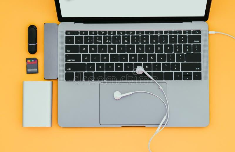 Portátil com tipo-c adaptador, movimentações instantâneas, fones de ouvido e banco de USB do poder isolado em um fundo amarelo fotografia de stock
