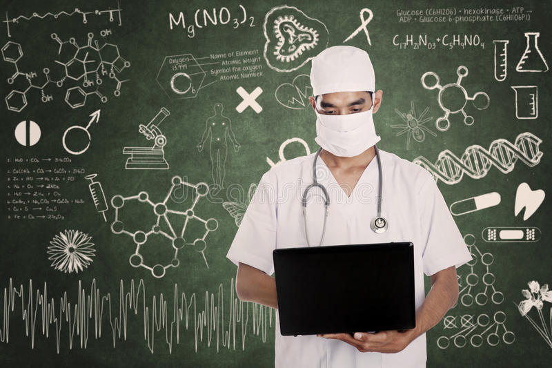 Portátil da posse do médico da saúde no quadro tirado