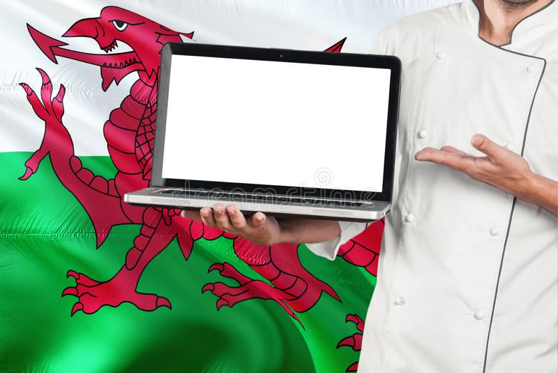 Portátil da terra arrendada do cozinheiro chefe de Galês com a tela vazia no fundo da bandeira de Gales Cozinhe o uniforme e o po fotografia de stock