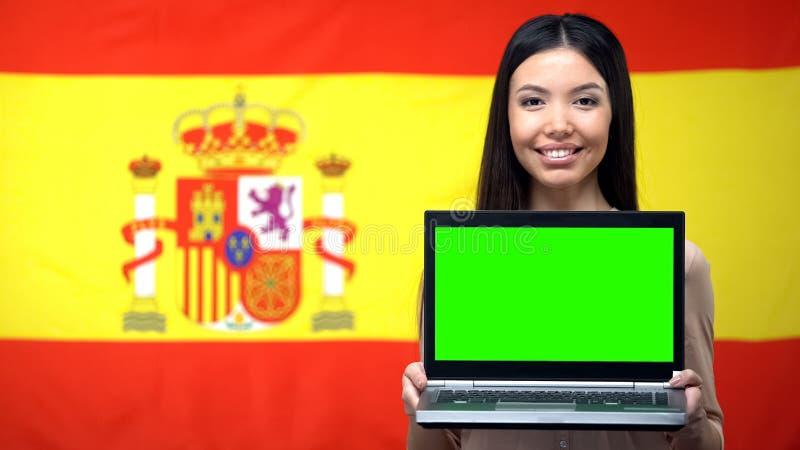Portátil da terra arrendada do estudante fêmea com tela verde, bandeira espanhola no fundo fotos de stock