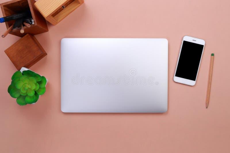 Portátil da vista superior, smartphone e artigos de papelaria do escritório no fundo pastel imagens de stock