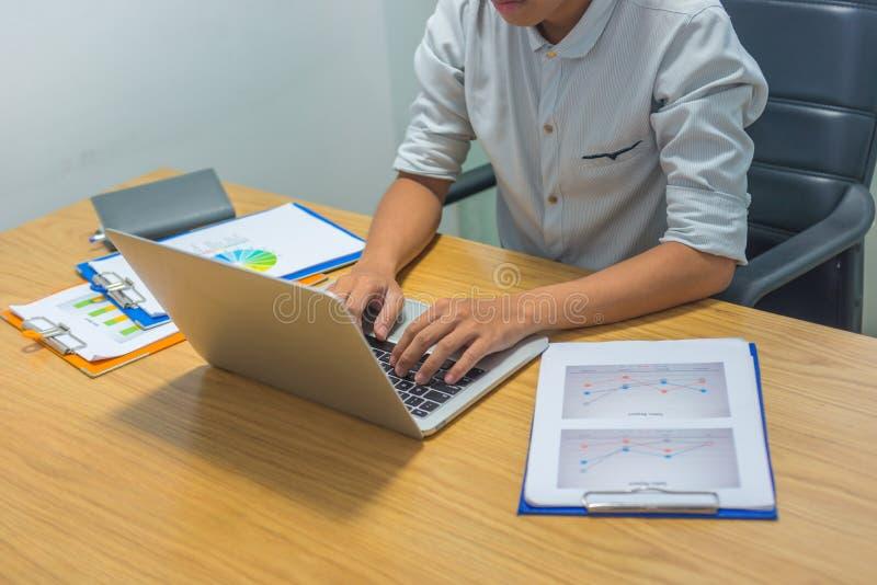 Portátil de datilografia da mão asiática do homem de negócios ao lado do documento da estatística imagens de stock