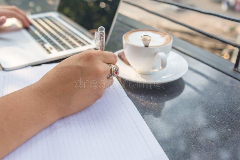 Portátil de datilografia do homem de negócios pela mão esquerda, escrevendo a nota pelo assistente foto de stock