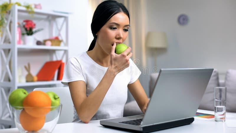 Portátil de trabalho da mulher bonita em casa, comendo a maçã verde, petisco saudável, vitaminas fotografia de stock