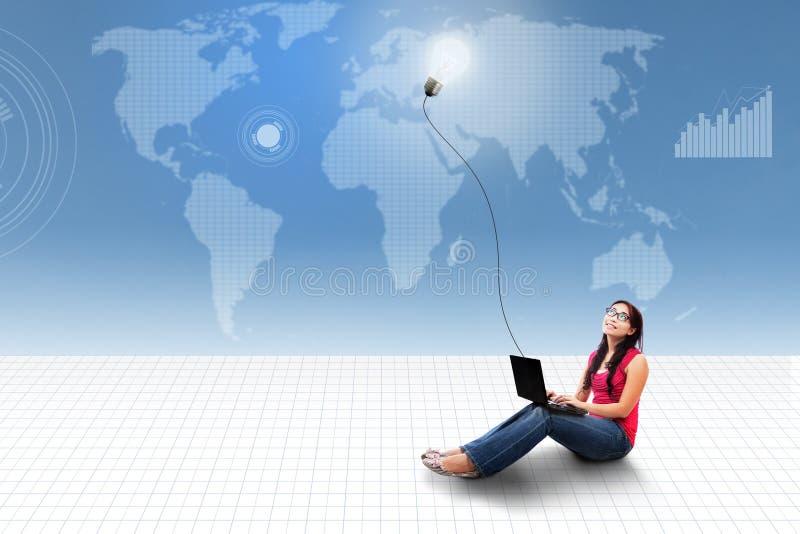 Portátil de utilização fêmea asiático no mapa do mundo fotografia de stock royalty free