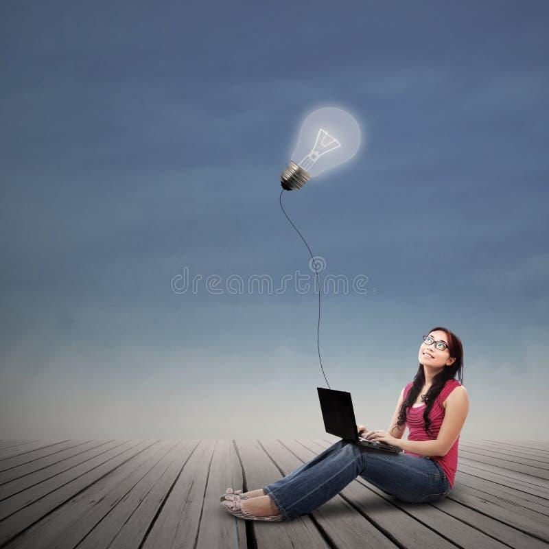 Portátil de utilização fêmea bonito sob o bulbo iluminado exterior ilustração do vetor