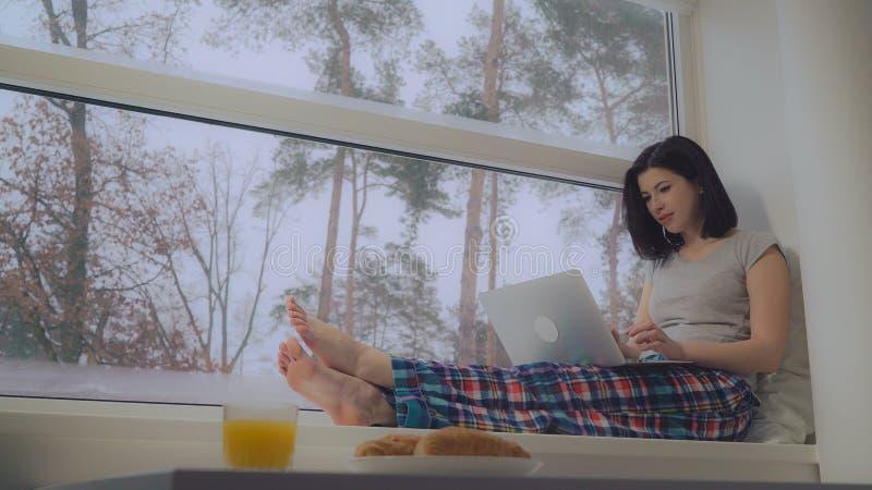 Portátil de utilização fêmea na manhã foto de stock royalty free