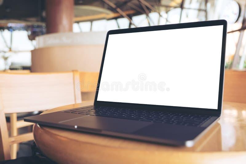 Portátil do computador com a tela branca vazia do desktop na tabela de madeira no café fotografia de stock